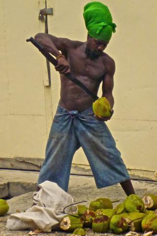 On the Street in Front of the Restaurant this Rastafarian Prepares its Coconuts