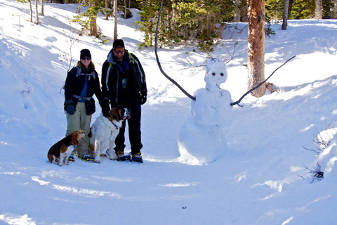 Two Humans, Two Dogs, One Snowman